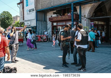 Editorial image of people at Eminonu Square in the middle of the day - police officers, man talking on the phone and random passerby.