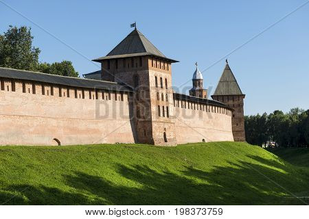 fortified brick wall of the Novgorod Kremlin 3 towers with Windows cone-shaped wooden roofs the medieval construction the covered with green grass