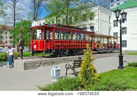 VITEBSK BELARUS - MAY 21 2017: Unidentified people walk near monument to first Vitebsk tram and monument to conductor Belarus