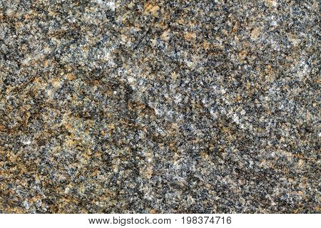Background of granite stone close-up. On gray background there are inclusions of yellow mineral.