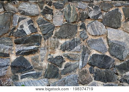 Masonry made of granite stone. Background. Wall is built of granite stone bonded with cement.