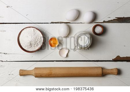 Baking background. Cooking ingredients for yeast dough and pastry, eggs, flour and milk on white rustic wood. Top view with copy space, mockup for menu, recipe or culinary classes. on the wooden table