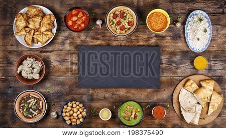 Assorted indian food on a wooden background. Dishes and appetizers of indian cuisine. Curry, butter chicken, rice, lentils, palak paneer, samosa, naan, chutney, spices. Bowls and plates with indian food