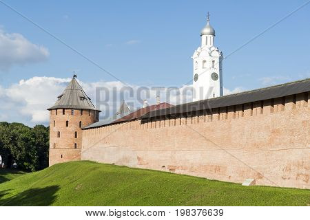 brick fortress wall of the Novgorod Kremlin round terracotta tower with the Windows the white tower with a dome and a clock the with the moat covered with green grass medieval building