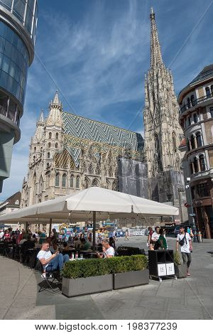 Vienna Austria - July 31 2017: Stephansplatz in Central Vienna with famous St. Stephens Cathedral. Tourists are walking around or relax in a restaurant on a sunny day