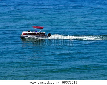 Pontoon boat with wake on lake, Muskegon Michigan