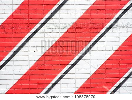 white brick wall pavement with red and black stripes