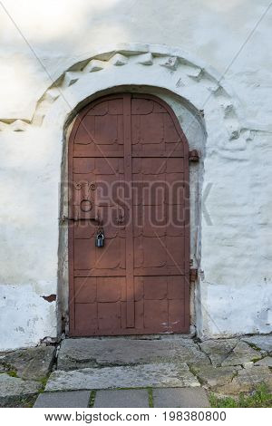 one 1 metal door deadbolt lock entrance exit white wall medieval building 11th century