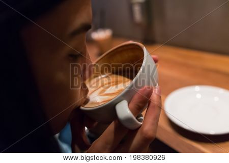 a girl is sipping the hot latte coffee in the morning