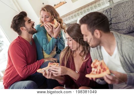 Couple sharing pizza and eating together in the livingroom.