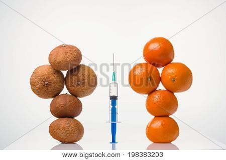 Wrinkled dried and smooth elastic tangerines in the form of a figure of the person and the syringe between them