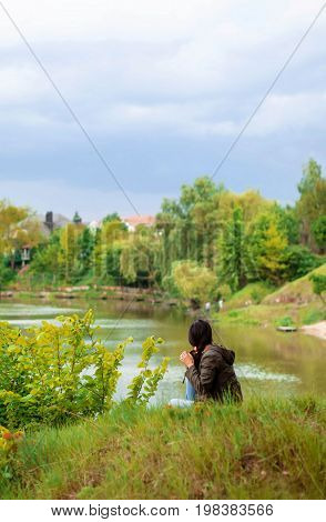 A young girl with long dark hair in a cloak with a hood sits on the river bank with her back and looks afar at nature.