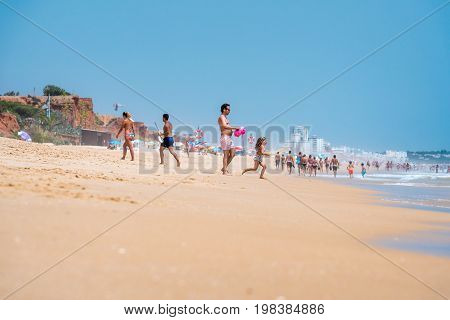 People on beach sunbathing. Albufeira Portugal - July 17 2017: Low angle side view of people on public beach at the Algarve coast who come to relax swim and sunbathing. A man and child playing in the foreground.