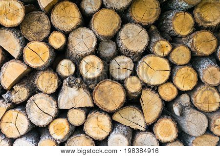 Background of dry chopped firewood logs stacked up on top of each other in a pile.