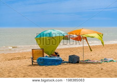 Two colorful sun parasols and a chair at a windy sunny beach in Algarve Portugal.