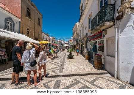 Perspective street view with people. Albufeira Portugal - July 19 2017: Perspective street view of the old parts av Albufeira city with tourists shopping and some about to go to the beach. Many shops and restaurants along the street.