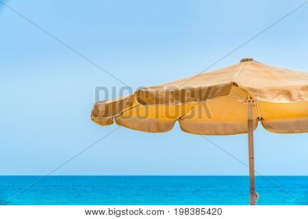 One yellow sun parasol against blue water and sky horizon with copy space.