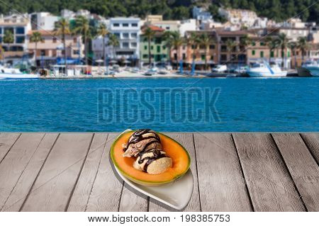 Melon filled with ice balls and garnish on a wooden table. In the background blue sea and a mediterranean harbor town.