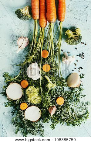 Raw vegetables for cooking soup. Ingredients young carrot with haulm, broccoli, cauliflower, onion, garlic, salt pepper over turquoise concrete background. Top view. Dinner cooking concept