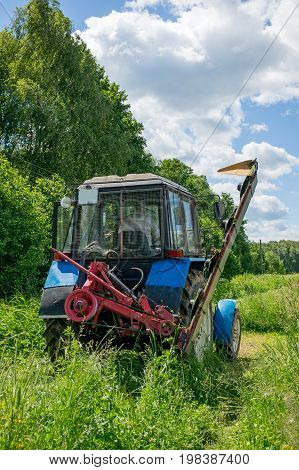 Farm tractor green mowing high grass in a Sunny summer day.