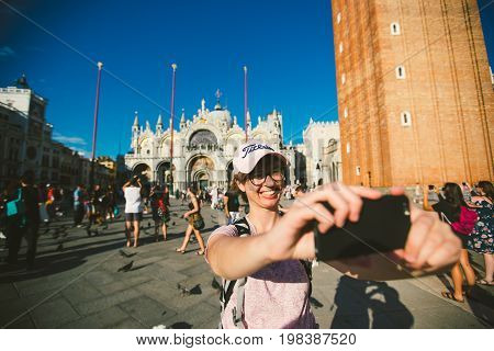 A girl in a cap and glasses makes selfi takes pictures of herself on a mobile phone in San Marco Square in Venice Italy in the summer. Tourist concept