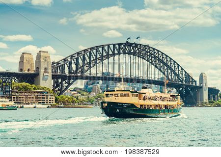 Sydney Australia - November 9 2015: Lady Northcott ferry with people onboard arriving at Cirqular Quay near Harbour Bridge on a warm sunny evening