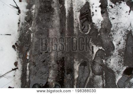 Groung melting snow mud dark gray brown puddle