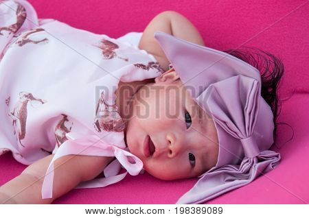 A shot of a cute baby girl with purple headband while sleeping and playing on the pink chair /  Focus at infant girl