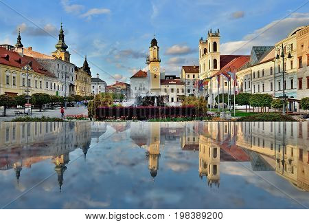 Spring city centre in Banska Bystrica. Historical buildings in Slovakia. Sunset in Square of Slovak National Uprising with blooming flowers. Reflection in stone pedestal