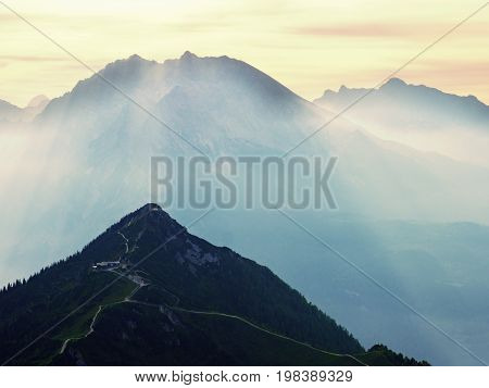 View Over Alpine  Cliff And Valley. Sun At Horizon, Blue Sky With Few Clouds. Alps Mountains