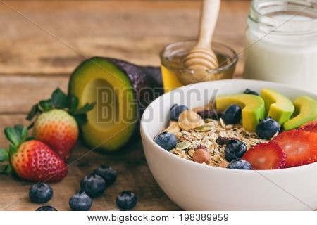 Muesli or granola on white bowl with fresh fruits nuts and cereal. Granola top with blueberries strawberries and avocado served with milk and honey for breakfast.Granola is healthy food for dieting. Homemade granola ready to served.