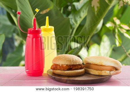 Hot dogs and chicken burgers on the wooden plate