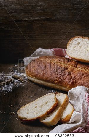 Homemade white wheat bread whole and slice served with wheat grain seeds and flour on white linen towel over dark wooden kitchen table. Rustic style.