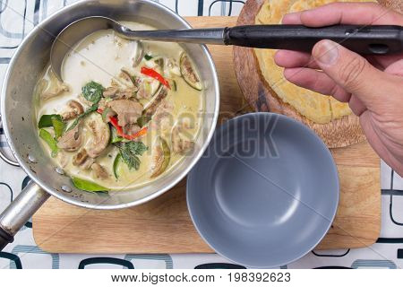 Chef putting beef green curry to the cup / Cooking green curry concept