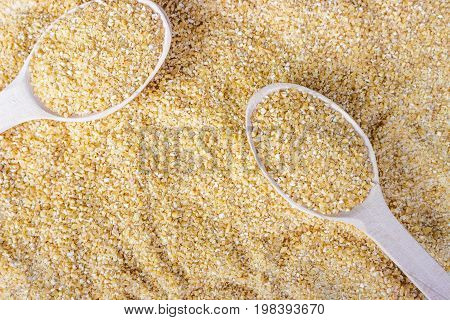 Barley groats on wooden spoon. Barley groats background. Top view.