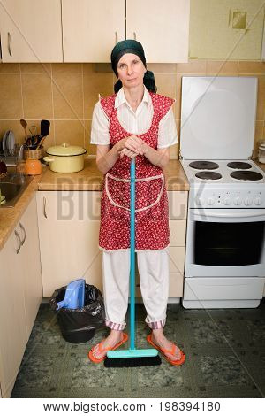 Woman With A Broom In The Kitchen
