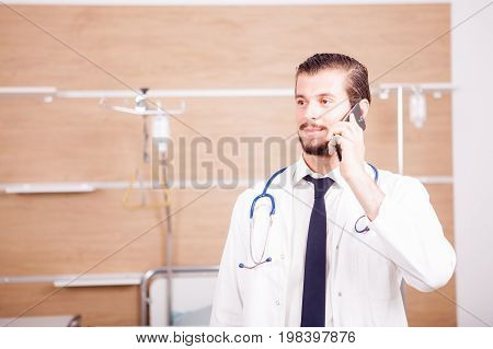 Doctor talking on the phone with stethoscope arround his neck in hospital recovery room. Medicine and healthcare