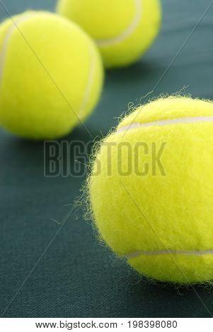 Three tennis yellow ball isolated on green