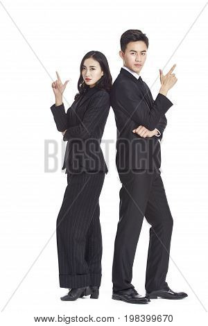 portrait of young asian businessman and businesswoman in formal businesswear showing hand sign of gun isolated on white background.