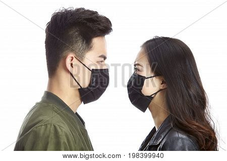 young asian man and woman wearing black mask staring at each other isolated on white background.