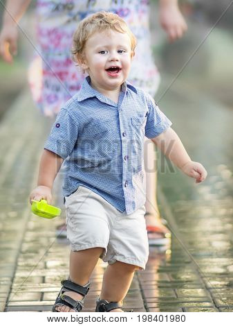 Playful happy funny little boy running away from his mother and laughing at summer day