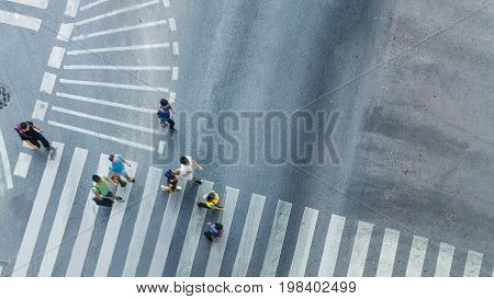 top aerial view of blur people walk to pedestrian crosswalk on road with the traffic pattern signage on the street.