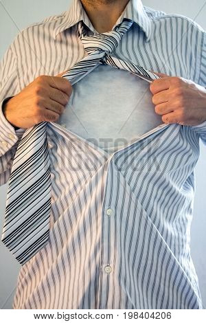 Businessman acting like a super hero tearing his shirt off with white space.