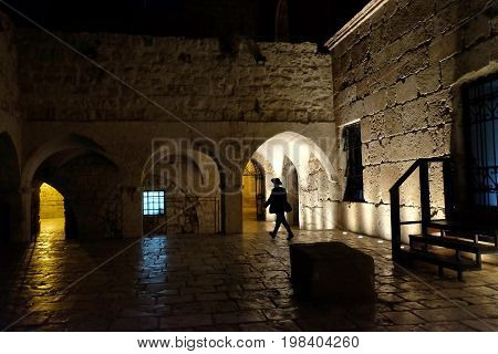 Religious Jew walks next to the Tomb of King David in Jerusalem