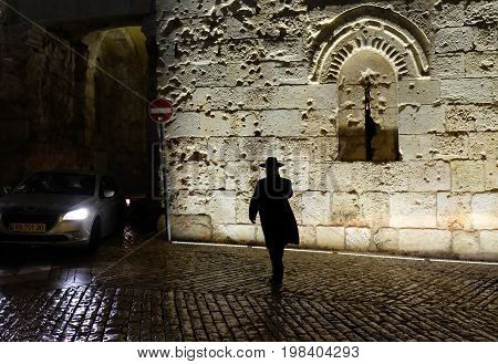 JERUSALEM ISRAEL - AUGUST 03 2017: Religious Jew walks into the Zion Gate of the Old City of Jerusalem at night
