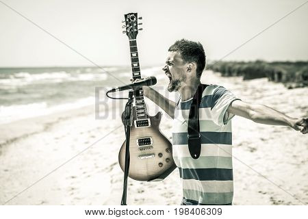 Rock On The Beach, The Musician Plays The Guitar And Sings Into The Microphone, The Concept Of Leisu
