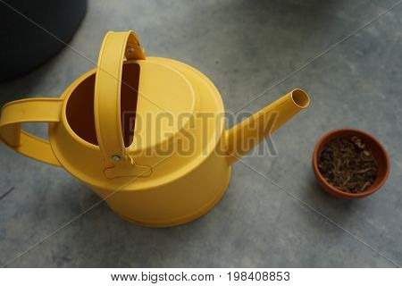 yellow watering can with dry ton pot giving water