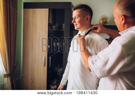 stylish groom dressing up, getting ready in morning for wedding ceremony, putting on cuff links