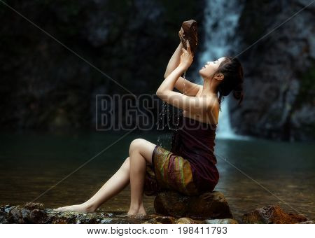 Asian woman in nature relaxation waterfall background