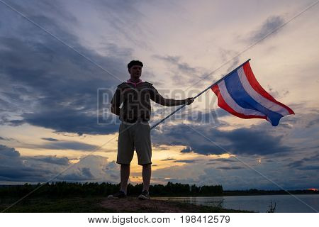 Scout header holding Thai flag silhouette on hill